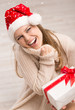 Cheerful Christmas lady with gift box looking at snow fall