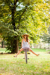 Beautiful girl is cycling in a park with a city bike