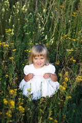 litle girl sitting in a meadow