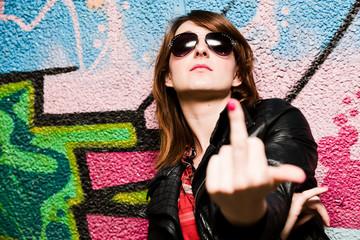 Stylish girl showing fuck off against graffiti wall