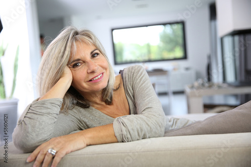 Mature woman relaxing at home in sofa