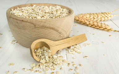 Wooden bowl and spoon with oatmeal flakes on wooden table
