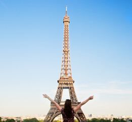 Young happy woman facing the Eiffel Tower, Paris, France