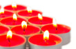 Glowing red tea lights on white