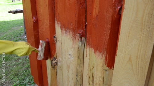 hand glove painting wooden plank house wall with brush red color
