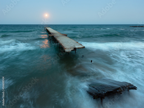 Night sea surf, ruined pier and Moon in sky (Black Sea, Bulgaria