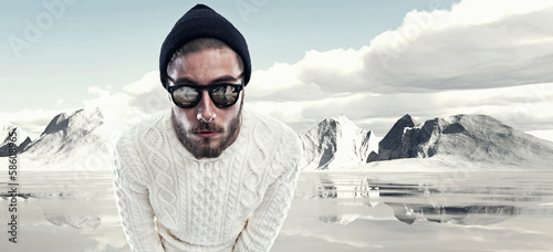 Cool man with beard in winter fashion. Wearing white woolen swea