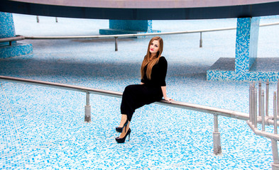 Sexy woman in black dress sitting on pipe of empty fountain