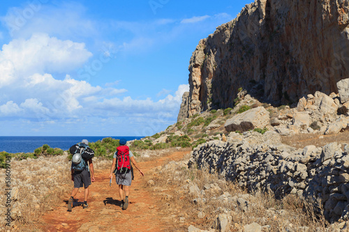 Two unidentified men walk the path to the rocks in Sicily