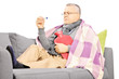 Sick mature man on a sofa with a hot-water bottle and termometer
