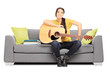Young female musician seated on a couch posing with a guitar