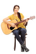 Young female musician on a chair holding an acoustic guitar