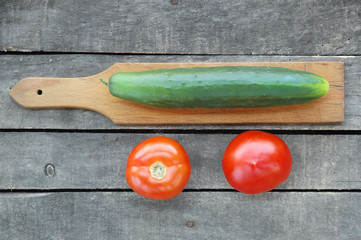 cucumber on cutting board with two tomatoes