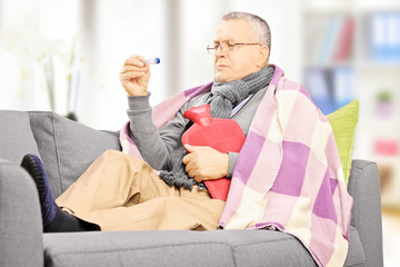 Sick man on a sofa with hot-water bottle looking at thermometer