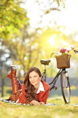 Young female with bicycle in a park on a sunny day