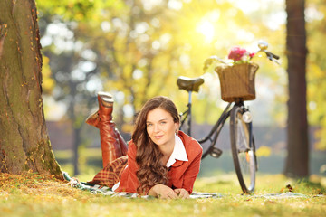 Young female lying on a green grass with bicycle on a sunny day