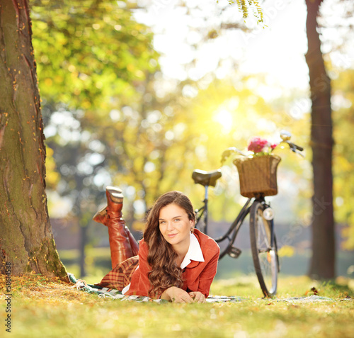 Young female relaxing on a grass with bicycle in a park