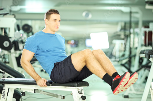 Young man on a bench exercising abdominal abs in a fitness club