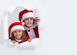 Happy kids in santa outfits looking through hole in paper