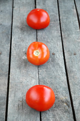 Three whole tomatoes on wooden background