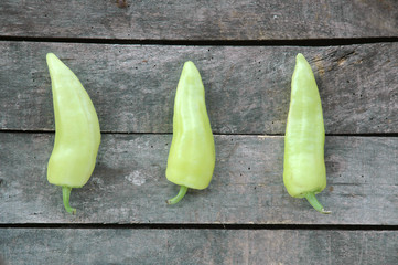Three green peppers on gray wooden background