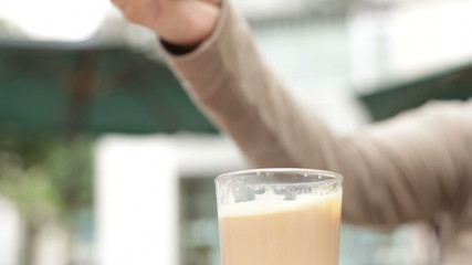 Hand with spoon stirring and pouring glass of coffee with milk.
