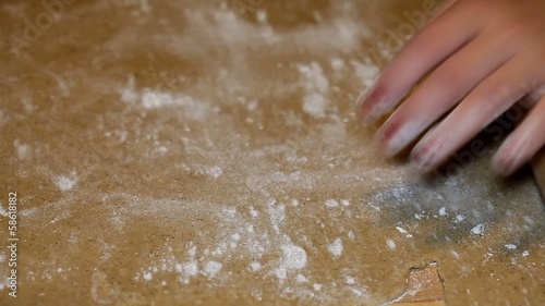 Woman rolling dough on a table using a roller