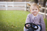 Young Toddler Smiling and Playing on Toy Tractor Outside