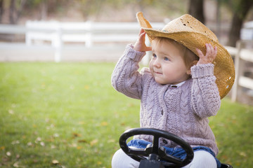Toddler Wearing Cowboy Hat and Playing on Toy Tractor Outside