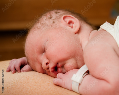 Portrait of infant resting on mother moments after birth