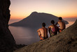 Three rock climbers having rest and watching sunset