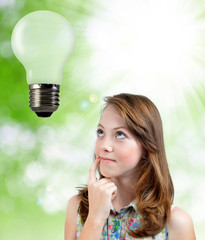 Thinking girl looking at the bulb