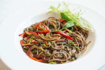 Close-up of buckwheat udon noodles with vegetable sauce