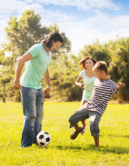 Happy parents with teenage son playing with  ball