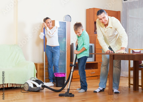 Couple with teenager dusting together