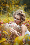 Beautiful fairy girl with golden cage in a forest