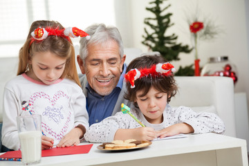 Man Looking At Children Making Christmas Greeting Card