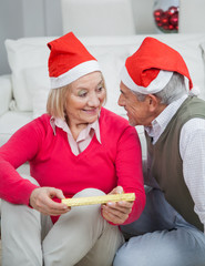 Senior Woman Holding Christmas Gift Looking At Man