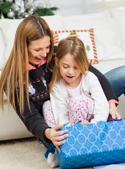 Mother And Girl Opening Christmas Present