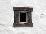 Old window on white wall of a house