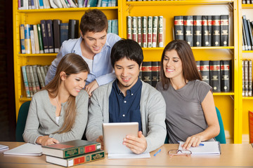 Students With Digital Tablet Studying Together In College Librar