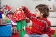 Boy Sitting By Stacked Christmas Gifts
