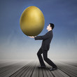 Businessman holding big golden egg