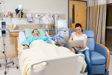 Woman With Digital Tablet Sitting By Patient
