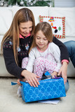 Mother And Daughter Opening Christmas Present