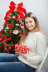 Woman With Gift Sitting By Christmas Tree