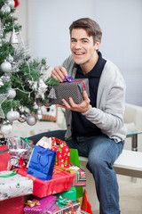 Happy Man With Gifts Sitting By Christmas Tree