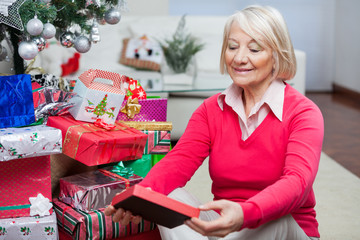 Senior Woman Looking At Christmas Gift