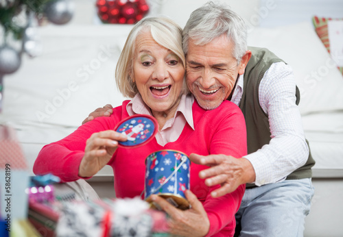 Surprised Senior Woman With Man Looking At Christmas Gift