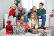 Children With Christmas Presents While Family Sitting On Sofa